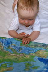 toddler studying a world atlas